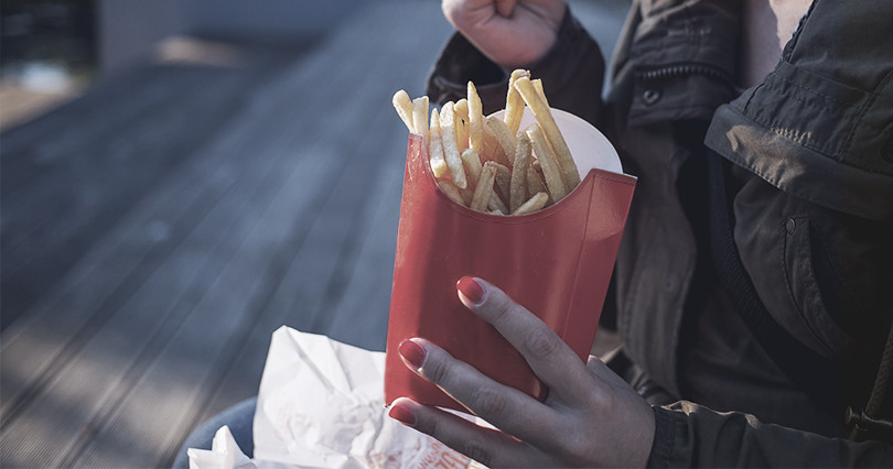 A women snacks on some french fries