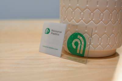 A single plastic business card printed on clear plastic with a vase visible behind