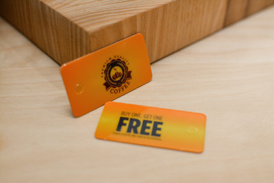 A small pile of orange and yellow coffee shop key tags that offer a buy on coffee and get another one free deal