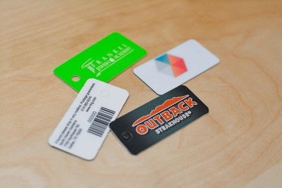 Three different key tag designs used by restaurants and schools that feature bright colors