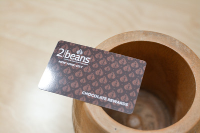 A dark brown pattern design used on plastic cards for a chocolate and coffee shop