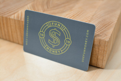 A dark gray plastic gift card design with a large dollar sign