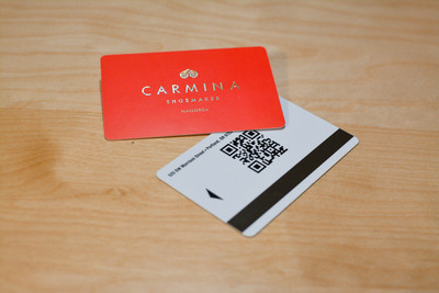 A bright red design with a metallic logo on the front and a QR code on the back